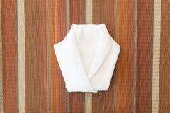 Den vita servetten vek in i en skjorta på matställetabellen Royaltyfri Bild