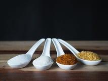Den vita skeden som överträffas med chilipulver, socker, saltar och vitlök Arkivbilder