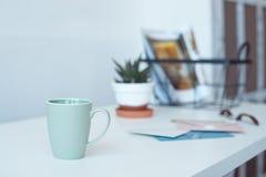 Den vita skrivbordtabellen med kopieringsutrymme, tillf?rsel och kaffe r?nar Workspace f?r fr?mre sikt och kopieringsutrymme arkivbild