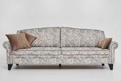 Den vita soffan med tappningstilmodeller och brunt kudde på den isolerade på vit bakgrund Royaltyfri Bild