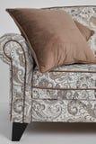 Den vita soffan med tappningstilmodeller och brunt kudde på den isolerade på vit bakgrund Arkivfoto