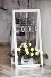 Den vita ställningen med blommor shoppar på ingången Arkivfoto