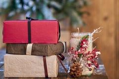 Den vita stearinljushållaren dekorerade med sörjer kotten och röda ashberry och röda, bruna och sandiga gula julgåvor på trätabel arkivbilder