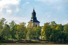 Den vita stenkyrkan med höst färgade omgeende träd arkivfoto