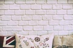 Den vita tegelstenväggen med kuddarna arkivfoton