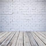 Den vita tegelstenväggen och trägolvet texturerar bakgrund Fotografering för Bildbyråer