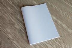 Den vita tidskriften ligger på en beige tabell royaltyfria foton