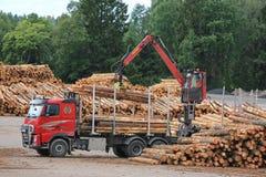 Den Volvo FH lastbilen lastar av journaler på bråtegården Arkivfoto