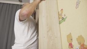 Den vuxna caucasian vita mannen hänger bokhyllan till väggen i barnrum Skallig manhängning bokhyllan i barnrum diy begrepp lager videofilmer