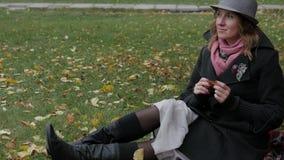 Den vuxna härliga kvinnan i en hatt går i hösten parkerar Den glade hösten går Royaltyfri Bild