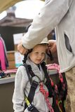Den vuxna instruktören sätter utrustning på en 5-årig pojke för extrema sportar arkivbild