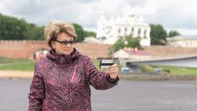 Den vuxna kvinnan åldrades 60-tal tar foto genom att använda smartphonen stock video