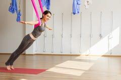 Den vuxna kvinnan öva aero anti--gravitation yogaposition i studio Royaltyfria Bilder