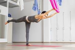 Den vuxna kvinnan öva att balansera position för pinneanti--gravitation yoga i studio Fotografering för Bildbyråer