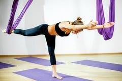 Den vuxna kvinnan öva att balansera position för pinneanti--gravitation yoga i studio Flickan sträcker med hjälp av hängmattan i  royaltyfri bild