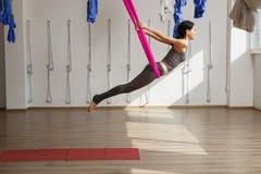 Den vuxna kvinnan öva position för inversionsanti--gravitation yoga i idrottshall arkivbilder