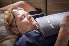 Den vuxna kvinnan avverkar sovande med en bibel i henne händer Arkivfoto