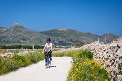 Den vuxna kvinnan cyklar på den Favignana ön, Italien Royaltyfri Fotografi
