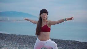Den vuxna kvinnan gör gymnastiska övningar utomhus i morgontid nära havet lager videofilmer