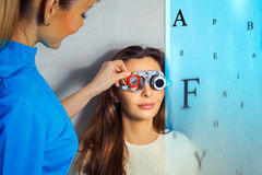 Den vuxna kvinnan kontrollerar vision i en ögonläkare med korrigerande Arkivbilder