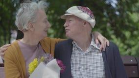 Den vuxna kvinnan rymmer en h?rlig bukett av blommor, medan hennes ?ldre make kramar henne Vuxna par f?r mjukt f?rh?llande arkivfilmer