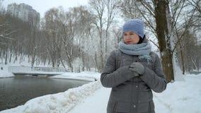 Den vuxna kvinnan som bara går i vinter, parkerar på snöig dag lager videofilmer