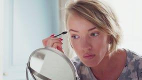 Den vuxna kvinnan som gör makeup, korrigerar eyebrowss lager videofilmer