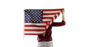 Den vuxna kvinnan står med hennes baksida och lyfter upp amerikanska flaggan på vit bakgrund lager videofilmer