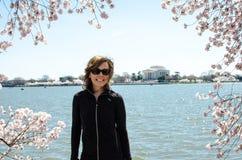 Den vuxna kvinnan står och poserar vid Cherry Blossom träd och Thomas Jefferson Memorial i Washington DC royaltyfria bilder