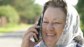 Den vuxna kvinnan talar på silvermobiltelefonen utomhus arkivfilmer
