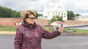 Den vuxna kvinnan tar foto genom att använda silver den smarta telefonen arkivfilmer