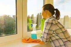 Den vuxna kvinnan tvättar fönster som gör ren huset, kvinnligblickar in i ett rent tvättat fönster royaltyfri fotografi