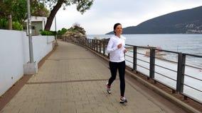 Den vuxna löparen joggar på kusten lager videofilmer