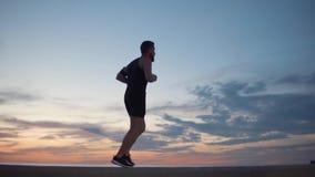 Den vuxna manliga joggeren kör mot molnig himmel i solnedgångtid lager videofilmer