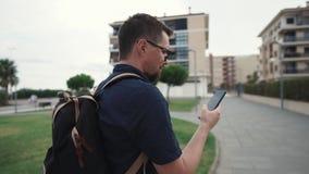 Den vuxna manliga turisten navigerar i stadsområde genom att använda den moderna smartphonen med översikter arkivfilmer
