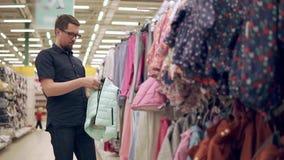 Den vuxna mannen betraktar ett varmt omslag för hans barn i ett klädlager lager videofilmer