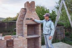 Den vuxna mannen bygger en tegelstenugn arkivbild