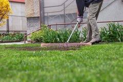 Den vuxna mannen försöker gör yttersida på samma nivå Sommararbetaren redigerar trädgården Mannen använder hjälpmedlet f royaltyfri foto
