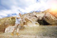 Den vuxna mannen fotvandrar med trekking poler Arkivfoto
