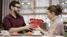 Den vuxna mannen ger blommor som han fick från en uppassare till hans fru, medan sitta i restaurang, och hon kysser honom stock video