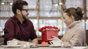 Den vuxna mannen ger en ask av blommor till hans lyckliga fru, och hon kysser honom lager videofilmer