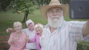 Den vuxna mannen i en hatt och ett grått skägg gör en selfie mot bakgrunden av hans vänner som sitter på en bänk i, parkerar stock video