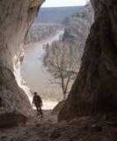 Den vuxna mannen i militär likformig i grotta nära vaggar floden arkivfoton