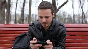 Den vuxna mannen lyssnar till musik på smartphonen i stad parkerar lager videofilmer