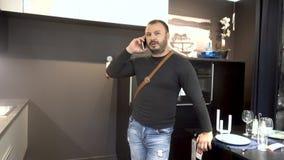 Den vuxna mannen med ett skägg använder en mobiltelefonsmartphone lager videofilmer