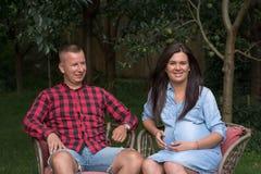 Den vuxna mannen och en gravid kvinna kopplar av i garden royaltyfri foto