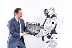 Den vuxna mannen och roboten delar inte portföljen royaltyfri fotografi