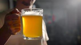 Den vuxna mannen rymmer fyllt öl rånar i mörkt rum som fäller ned därefter det, bartendern framlägger nytt öl arkivfilmer
