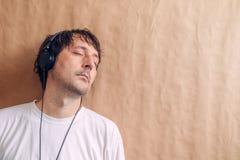 Den vuxna mannen som tycker om att lyssna till favorit- musik, podcast på headp arkivfoto
