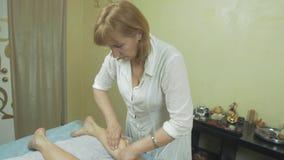 Den vuxna massösen gör att läka massage av vänster fot till den unga kvinnan i salong arkivfilmer